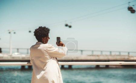 Photo pour Vue de derrière d'une jeune touriste noire aux cheveux frisés afro, dans une tranchée blanche et aux cheveux frisés afro prenant des photos de visites et de câbles au-dessus de l'eau ; un espace de copie à droite - image libre de droit