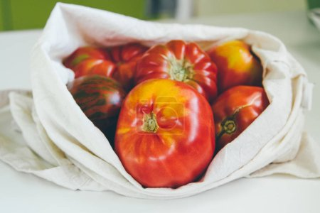 Photo for Canvas eco tote with red tomatoes. Local market vegetables. Eco friendly grocery bag - Royalty Free Image