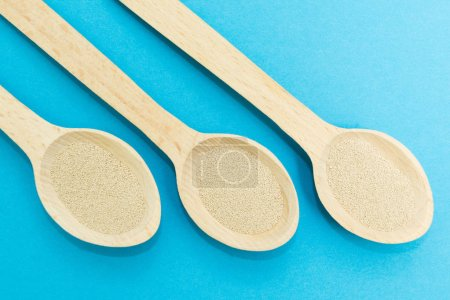 Three wooden spoons with instant dry yeast isolated on a blue background.