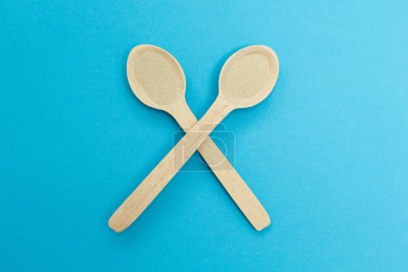 Two wooden spoons with instant dry yeast isolated on a blue background. Yeast is the main ingredient of fresh dough for pastry, pizza dough and many other dough.