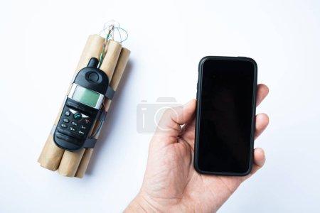 Bombe artisanale sur fond blanc et téléphone en main pour le contrôle .