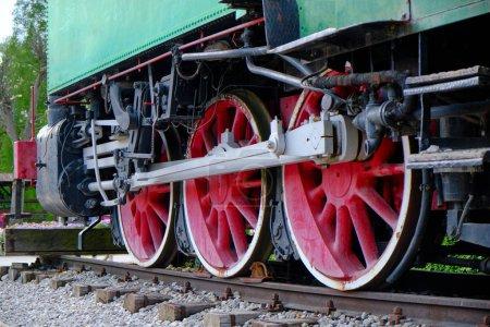 Détail locomotive vapeur vintage avec manivelles et roues rouges