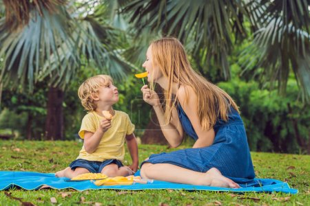 Mom and son had picnic in park. Eat healthy fruits - mango, pineapple and melon. Children eat healthy food.
