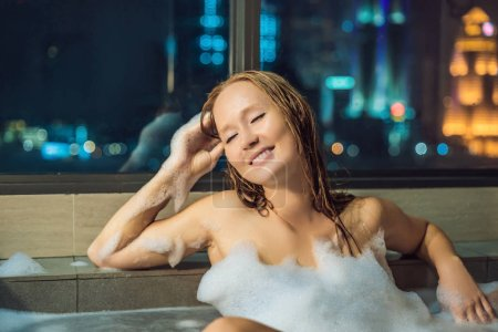 Young woman sits in bath with foam and frangipani flowers against background of panoramic window overlooking skyscrapers and big evening city