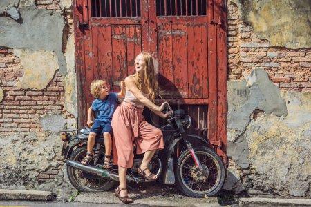 Photo pour Mère et fils sur une vieille moto. Penang, Malaisie. - image libre de droit