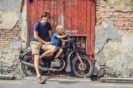 Photo pour Père et fils sur une vieille moto. Penang, Malaisie. - image libre de droit
