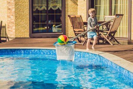 Toddler boy cleans the pool and pulls the ball out of the pool. Pool Cleaner Concept.