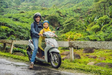 Father and son are traveling on a moped on a tea plantation in Malaysia. Traveling with children concept.