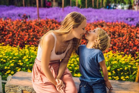 Beauty young mother and cute little son on flowers greenhouse