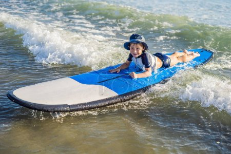 Happy baby boy - young surfer ride on surfboard with fun on sea waves. Active family lifestyle, kids outdoor water sport lessons and swimming activity in surf camp. Summer vacation with child.
