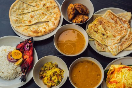 Assorted Indian food on dark wooden background. Dishes and appetizers of Indian cuisine. Curry, butter chicken, rice, lentils, paneer, samosa, naan, chutney, spices. Bowls and plates with Indian food.