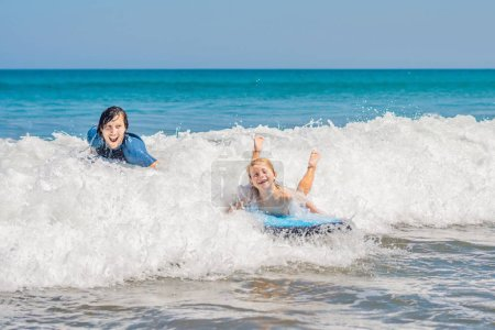 Father teaching his young son how to surf in the sea on vacation or holiday. Travel and sports with children concept.
