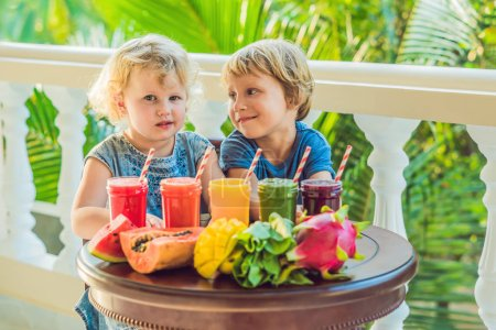 Photo for Children drinking colorful healthy smoothies. Watermelon, papaya, mango, spinach and dragon fruit. - Royalty Free Image