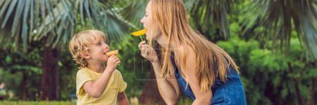 Mom and son had a picnic in the park. Eat healthy fruits - mango, pineapple and melon. Children eat healthy food. BANNER, long format