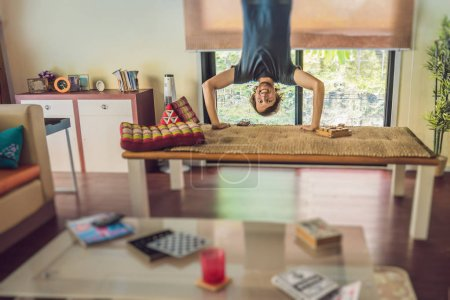 A man stands on his hands upside down in the living room.