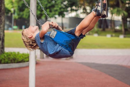Funny kid boy having fun with chain swing on outdoor playground. child swinging on warm day. Active leisure with kids. Boy wearing casual colorful school kid clothes.