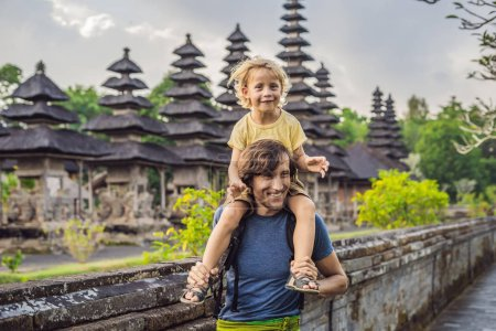 dad and son tourists posing by Taman Ayun Temple. Bali, Indonesia