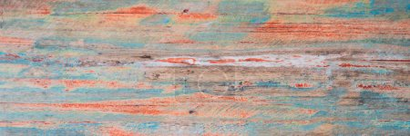 grungy weathered wooden surface covered with old blue and red peeling paint