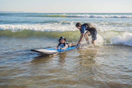 Father teaching son to surf in ocean on Bali island, Indonesia