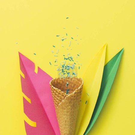 Photo for Waffle cone of ice cream among palm tropical leaves made of paper on yellow background. Summer vacation party concept - Royalty Free Image