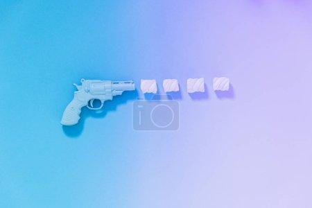 Photo pour Le canon tire trois guimauves au lieu de balles sur un dégradé et fond holographique . - image libre de droit