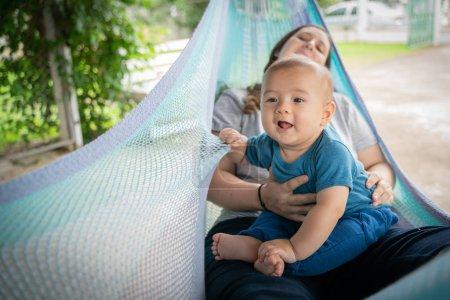 Photo pour Le petit garçon et la mère sont assis au hamac - image libre de droit