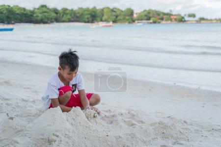 Photo pour Un enfant jouant dans le sable sur la plage - image libre de droit
