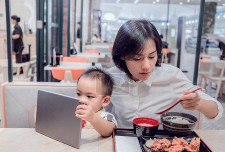 Photo pour La mère asiatique mange dans un restaurant. Pendant que son fils regardait la tablette avec intérêt.Focus sur le visage de bébé - image libre de droit
