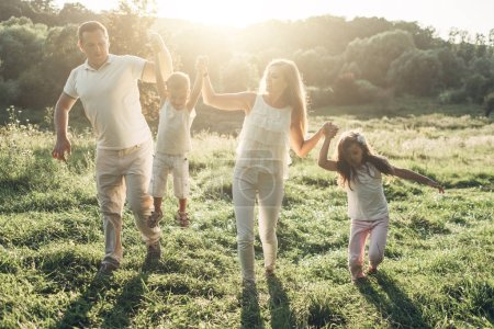 Photo for Adult couple with their little children having picnic in the Park Outside the City, Family Weekend Concept, Four People Enjoying Summer - Royalty Free Image