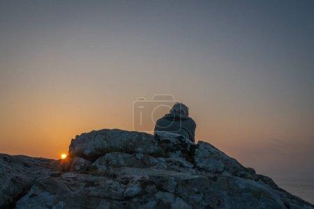 Photo pour St. Ives, Angleterre - Mai 2018 : Homme assis sur un rocher et admirant le coucher du soleil sur la côte cornique, Cornouailles - image libre de droit