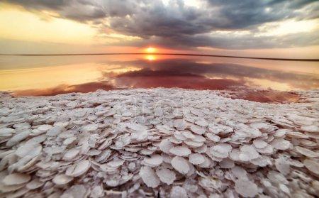 Photo pour Grandes plaques de sel au premier plan d'un lac rose salé au coucher du soleil. Vue fantastique du lac rose. Ukraine. - image libre de droit