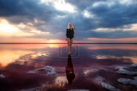 Photo pour Fille dans le noir dans l'eau d'un lac rose foncé au coucher du soleil. Dvushka et paysage fantastique. - image libre de droit