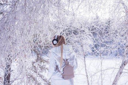 Photo pour La jeune fille écoute de la musique et se promène dans un beau parc d'hiver. Belle vue d'hiver des arbres dans le hoarfrost étincelant. - image libre de droit