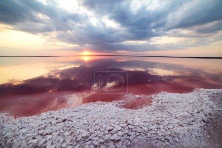 Photo pour Coucher de soleil fantastique sur un lac salé rose. De gros cristaux de sel ont une forme intéressante sur le rivage et se reflètent dans l'eau rouge du ciel au coucher du soleil.. - image libre de droit