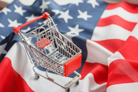 Photo for Shopping cart on the national flag of United States of America, background, top view - Royalty Free Image