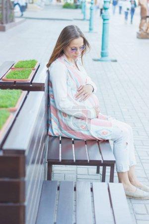 Photo pour Femme enceinte s'assoit sur le banc, fond de mise au point douce - image libre de droit