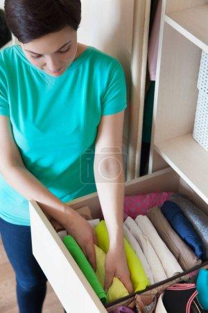 Photo pour La femme plie t-shirts dans le tiroir. Une femme est le rangement du placard. Stockage vertical des vêtements. - image libre de droit