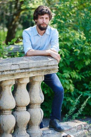Photo pour Bel homme barbu portant chemise et pantalon se penchant sur la barrière de Pierre et regardant la caméra dans le parc de l'été - image libre de droit