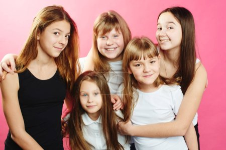 Photo for Group of cute girls hugging while posing on pink background - Royalty Free Image