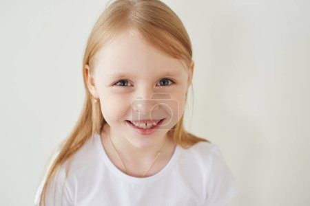 Portrait of little blonde girl in white t-shirt toothy smiling and looking at camera on white studio background, close-up