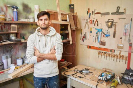 young man with crossed arms standing in home workshop, concept of make repairs in apartment