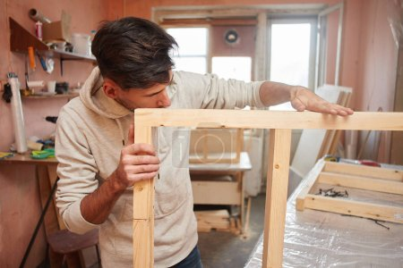 young man with wooden window frames standing in home workshop, concept of make repairs in apartment