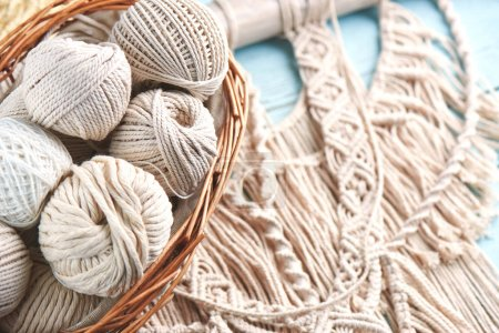 macrame threads in basket on wooden background, close-up