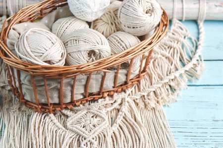 Handmade macrame braiding with threads in basket on wooden background, close-up