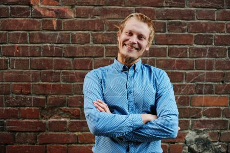 Photo for Portrait of smiling blond man with beard in blue shirt standing with crossed arms on red brick wall background - Royalty Free Image