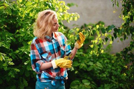 Photo pour Femme avec des sécateurs coupe branche d'arbre dans le jardin - image libre de droit