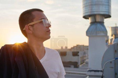 Foto de Hombre guapo con pie blanco de camiseta en azotea con paisaje de fondo - Imagen libre de derechos