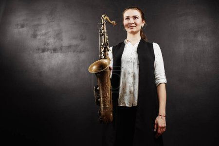 Photo for Woman holding saxophone on black background - Royalty Free Image