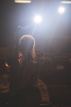 Photo pour Femme avec saxophone sur scène avec projecteurs sur fond - image libre de droit