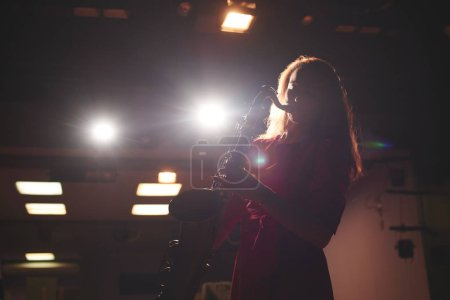 Photo for Musician woman in red dress playing saxophone on dark stage - Royalty Free Image